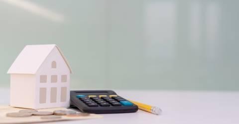 Papieren huis met een rekenmachine, potlood en muntgeld